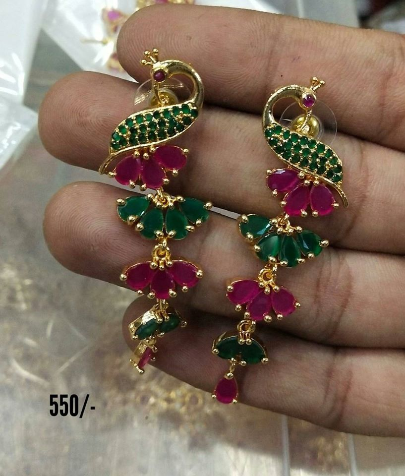 Beautiful and simple earrings studded with green and pink color stones. Earrings in peacock design.