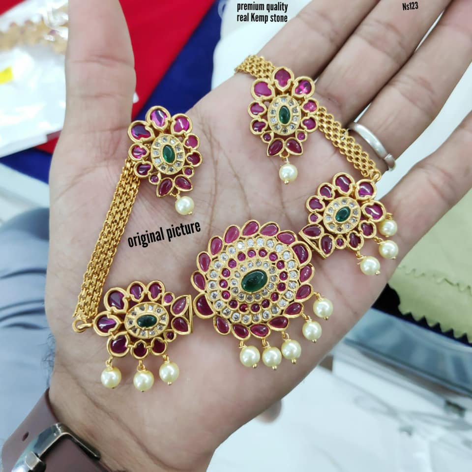 Gorgeous one gram gold choker studded with multi color stone and pearl hangings. Choker with matching earrings.
